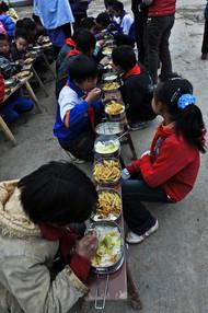 """有这样一群山里娃,他们每天步行一两个小时上学,怀揣的红薯土豆馒头就是中午在校的干粮,老师不敢在教室里吃饭,害怕学生们渴望的目光。有这样一群志愿者,他们来自媒体等各行各业,借助媒体和公益组织的力量,发起""""免费午餐""""项目,只为了让山里的孩子们在学校能吃上真正的午餐。2011年4月2日,贵州黔西县花溪乡沙坝小学""""免费午餐""""计划开启。沙坝小学的孩子开心接过自己的第一份""""免费午餐"""""""