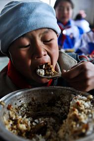 """2011年4月2日,贵州黔西县,沙坝小学的孩子大口的吃着""""免费午餐"""""""