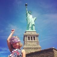 """7月""""美国独立日""""中,一名头戴镶有人造宝石粉红色头冠的可爱的小女孩在纽约自由女神像前摆姿势  纪实摄影:Instagram 2012年10大照片"""