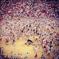 """""""西班牙斗牛节""""的现场,一头黑色公牛直冲向成千上万的观众和参加者,并且攻击了至少两个人的背部。  纪实摄影:Instagram 2012年10大照片"""